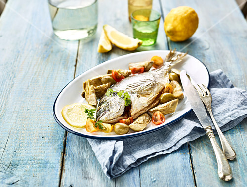 Sea bream baked in the oven with green olives and cherry tomatoes