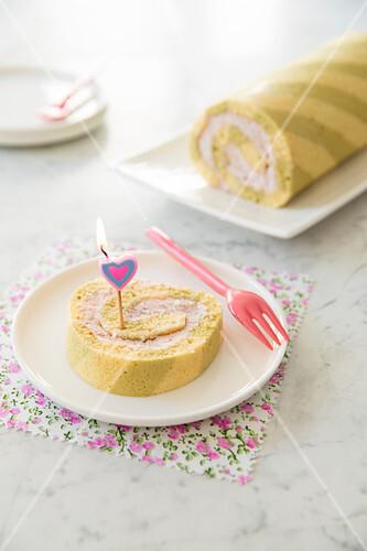 Matchatee-Erdbeer-Biskuitrolle mit herzförmiger Geburtstagskerze