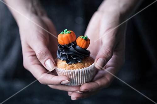 Hände halten einen Halloween-Cupcake