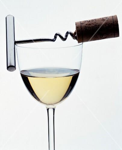 Glass of white wine with corkskrew