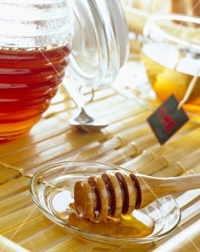 Honey stick, pot of honey and cup of tea