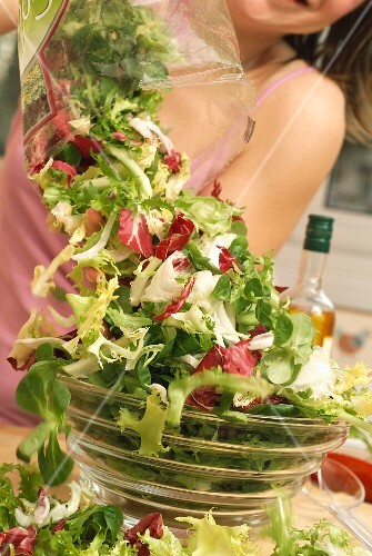 A mixed salad being transferred from a plastic bag into a salad bowl
