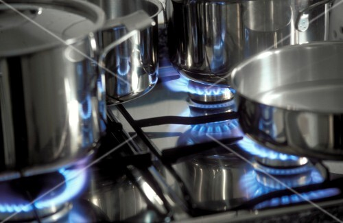 Gas stove with pans and blue flames