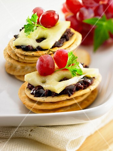 Crackers with cheese, red grapes and black olives