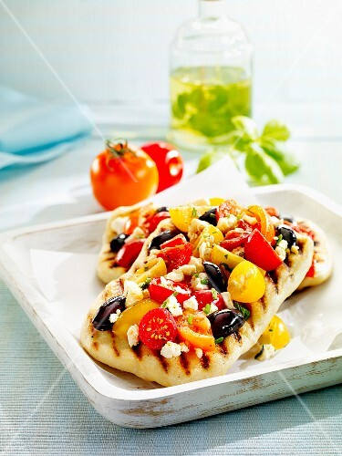 Pizza with feta cheese, olives and two types of tomatoes