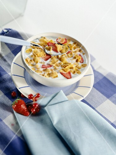 A bowl of cornflakes with strawberries