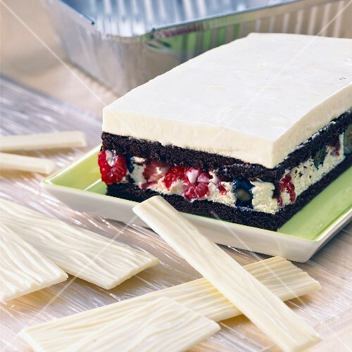 A square cake made from white and dark chocolate with fruits of the forest