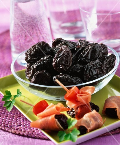 Dried plums and rolls of ham