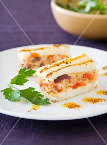 A layered cake with grilled fish and tomato pilau