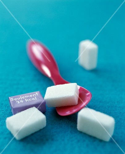 Sugar cubes and a pink plastic spoon