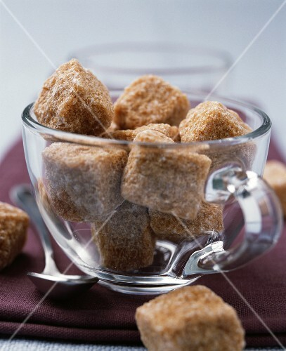 Lumps of brown sugar in a glass cup