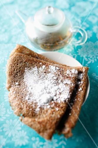 Buckwheat pancake with icing sugar and a teapot