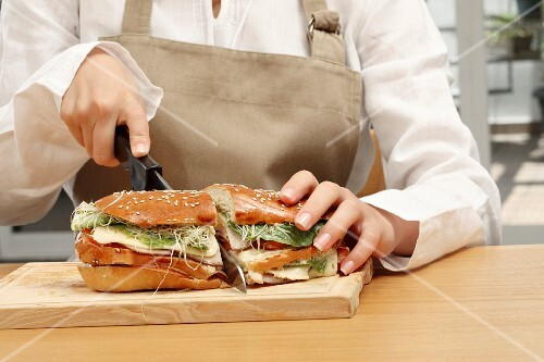 Woman cutting in two a turkey ham, cheese and vegetable milkbread sandwich