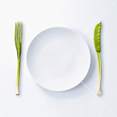 Empty plate and knife and fork made out of green vegetables