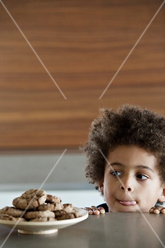 Young boy licking his lips infront of a plate of delicious cookies