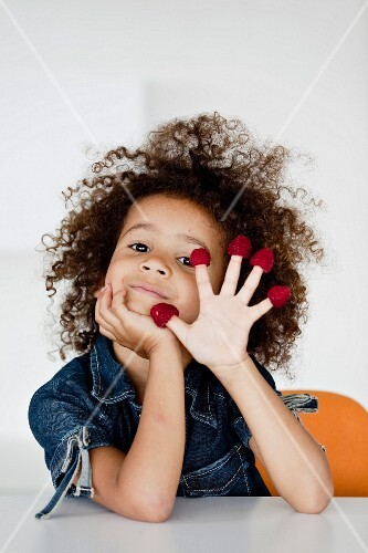 Young girl playing with raspberries
