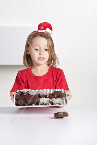 Young girl carrying a tray of chocolate biscuits