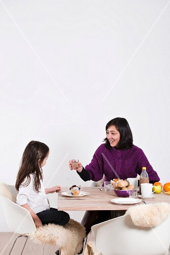 Mother and daughter having breakfast together