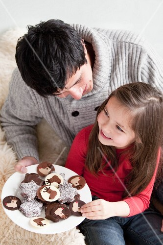Man offering a plate of chocolate cookies to a young girl