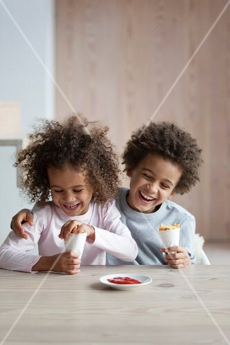 Boy and girl eating cones of french fries and ketchup