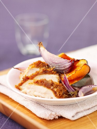 Sliced chicken breast coated in breadcrumbs with roast vegetables
