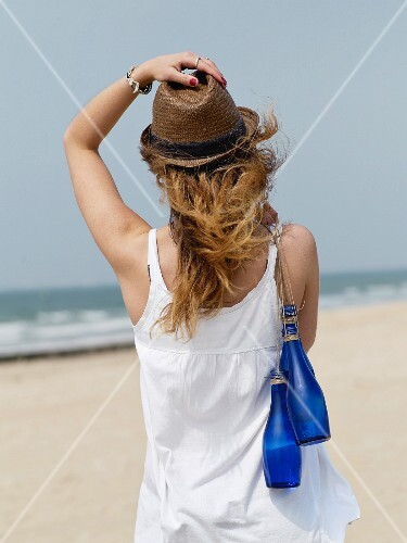 Young woman carrying blue glass bottles of water