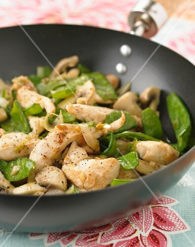 Chicken,sugar peas and button mushrooms cooked in a wok