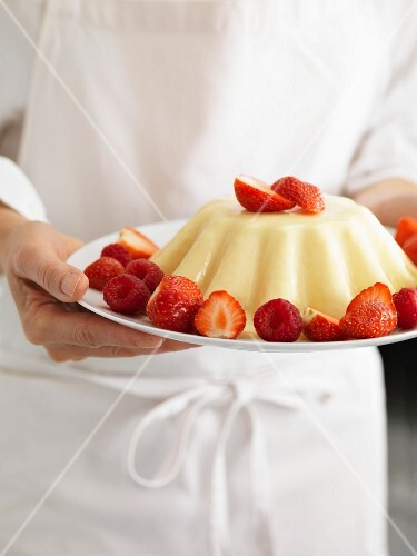 Person holding a plate of entremets with strawberries and raspberries