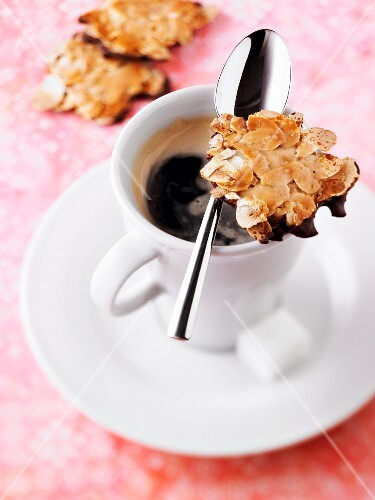 Chocolate and thinly sliced almond cookies and a cup of coffee