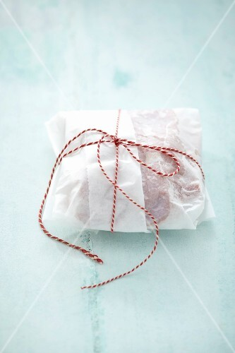 Piece of raw veal wrapped in paper and tied with a piece of string