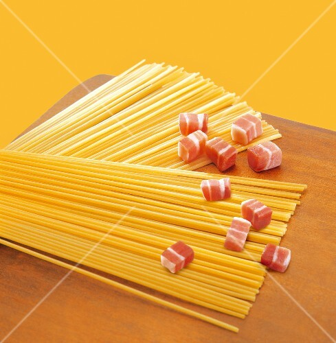 Uncooked spaghetti and raw diced bacon