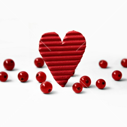 Red cardboard heart and redcurrants