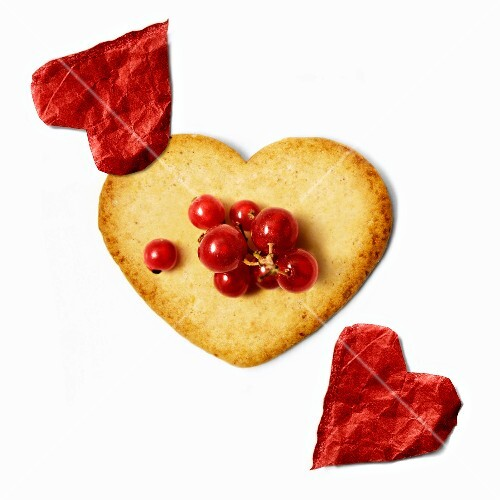Heart-shaped biscuit with redcurrants and red paper hearts