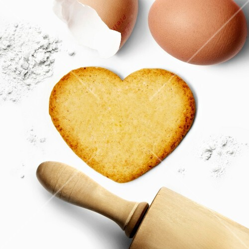 Heart-shaped biscuit with eggs,flour and a rolling pin