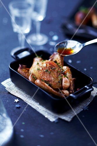 Pouring gravy over the young pigeon roasted with garlic and thyme