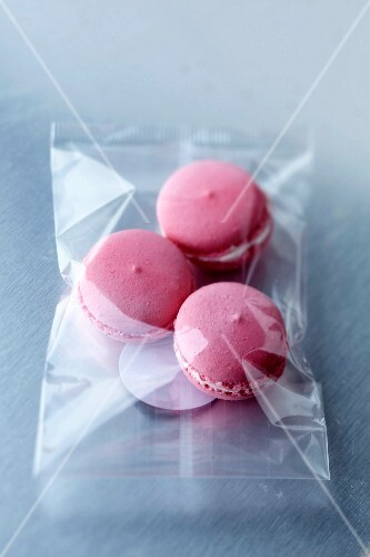 Three raspberry macaroons in a bag
