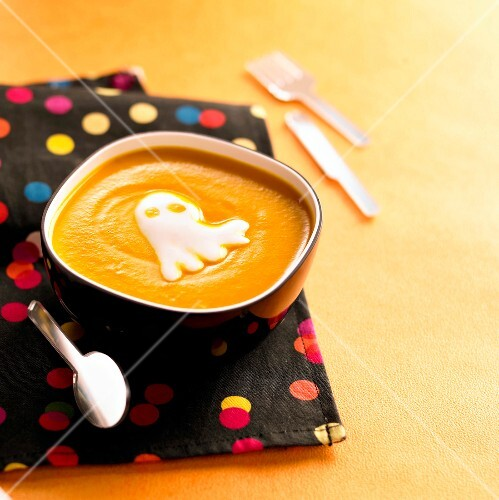 Cream of pumpkin soup with Halloween ghost-shaped whipped cream