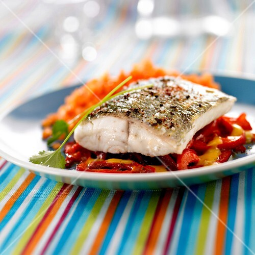 Piece of pike with red and yellow peppers