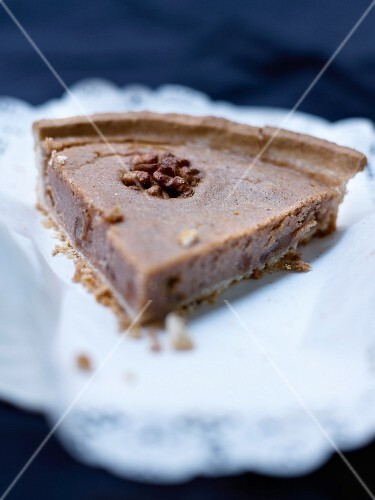 A slice of shortcrust tart with chestnut cream and walnuts