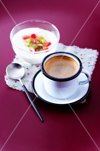 Cup of expresso coffee and a bowl of yoghurt with fresh fruit
