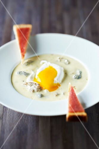 Poached egg in creamy morel sauce,fingers of bread with mountain raw ham