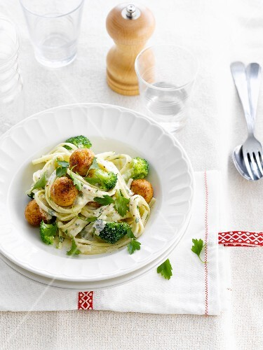 Pasta in creamy sauce with breaded turkey meatballs and broccolis