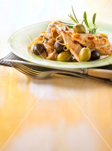 Sliced chicken breasts with green and black olives,lemon and rosemary