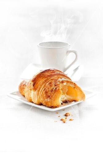 Half-eaten Croissant and coffee
