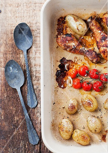 Roasted chicken drumsticks with potatoes and cherry tomatoes