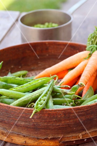 Spring peas and carrots in a sieve