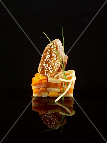 Soft carrot,glazed pork and sesame seed construction on a black background