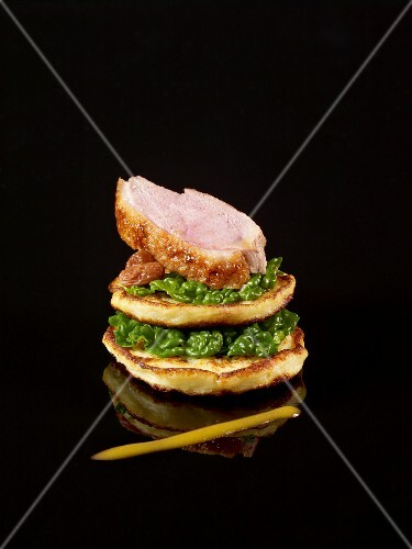 Layered blinis,cabbage and sliced duckling with orange coulis on a black background