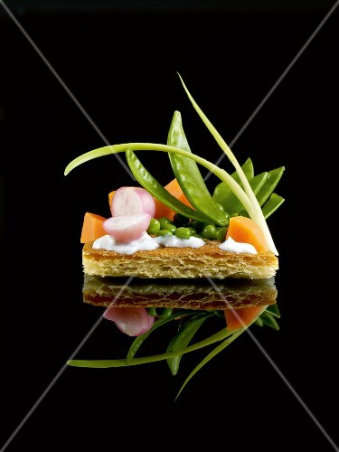 Small thin pastry vegetable tart on a black background