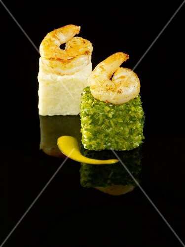 White and green risotto cubes topped with king prawns on a black background